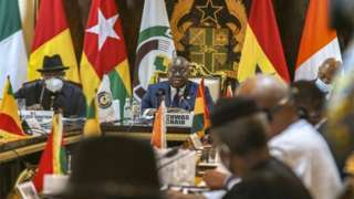 Ecowas and CNSP representatives sit at table surrounded by flags and other emblems of state in Accra, Ghana.