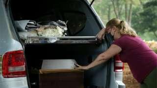 Mulher de máscara chora encostada em carro com caixão dentro