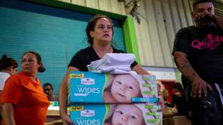 A woman carries boxes of baby wipes she removed from a warehouse filled with supplies in Ponce, Puerto Rico on January 18, 2020