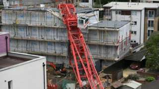 A crane crashed on to the development and two terrace houses in Compton Close, Bow