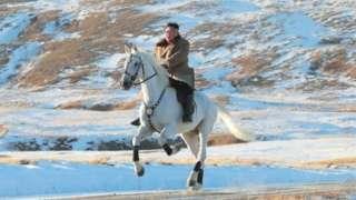 Kim Jong-un ku mugongo w'indogobe y'igitare ku musozi wuzuye urubura wa Paektu