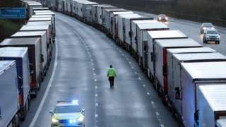 Police patrol along the M20 in Kent where freight traffic is parked up near to Folkestone services whilst the Port of Dover remains closed.