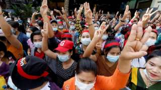 Protesters flash the three-finger salute, a symbol of resistance, as they demonstrate against the military coup in Yangon