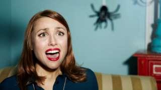 امرأة مرعوبة من منظر عنكبوت متدلي