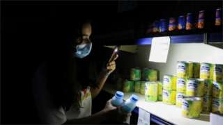A women uses her phone light in a shop in Lebanon during a power cut