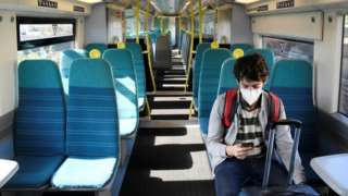 A man on a train with a mask on