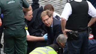 Conservative MP Tobias Ellwood helps emergency services attend to a police officer outside the Palace of Westminster