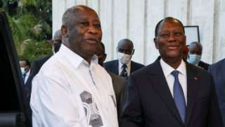 """Ivory Coast""""s President Alassane Ouattara shakes hands with former President Laurent Gbagbo"""