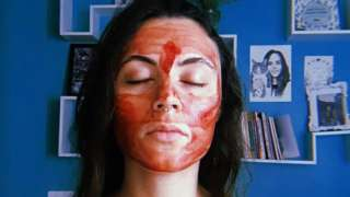 A picture of 27-year old Laura Mocellin Teixeira with her eyes closed, and her face and chest painted with menstrual blood