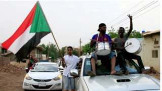 """Sudanese demonstraters wave their national flag as they celebrate in Khartoum early on August 3, 2019, after Sudan""""s ruling generals and protest leaders reached a """"full agreement"""" on the constitutional declaration."""