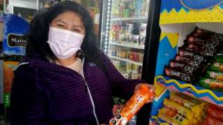 Rosa Cayso Phocco holds a packet of biscuits with a warning label in Chile