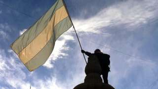 Bandeira argentina na contraluz, segurada por estátua