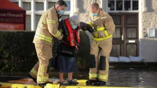 Firefighters helping people to safety