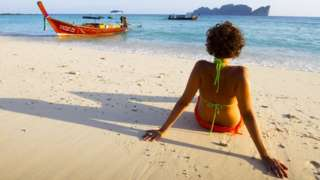 A woman relaxes on a beach in Thailand. File photo