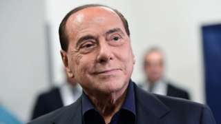 Silvio Berlusconi smirks, looking confident, at a polling station after casting his vote