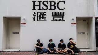 Protesters sit outside a HSBC in the Kowloon district of Hong Kong on August 11, 2019, in the latest opposition to a planned extradition law that was quickly evolved into a wider movement for democratic reforms