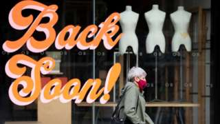 A woman wearing a Covid mask walking past a shop saying 'Back soon' in Cardiff