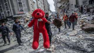 A Palestinian holds a teddy bear from the rubble of a destroyed houses after an Israeli air strike in Gaza City