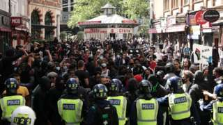 Police form a barrier in front of anti-racist protesters near Leicester Square