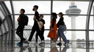 People wearing masks walk through Singapore Airport