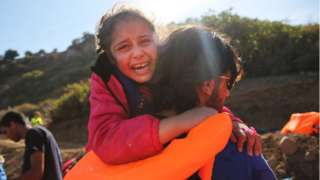 A young girl is helped moments after she arrived with other Syrian and Iraqi migrants on the island of Lesbos in 2015