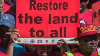"""A demonstrator in South Africa holds a placard reading """"Restore the land to all"""" as thousands of workers take part in a national strike called by the country's second largest labour union - April 2018"""