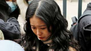 Zhou Xiaoxuan, also known by her online name Xianzi, weeps as she arrives at a court for a sexual harassment case involving a Chinese state TV host, in Beijing, China December 2, 2020.