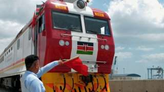 Man waving a red flag during the launch of the first batch of Standard Gauge Railway freight locomotives at Mombasa Port - January 11, 2017