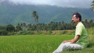 Sridhar sitting near a paddy field