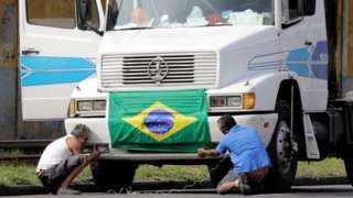 Truck drivers arrange a national flag in front of their truck to attend a protest against high diesel prices, near the port of Santos in Santos, Brazil May 23, 2018.