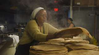 Zenebech Dessu prepares injera, an East African sourdough-risen flatbread at her Zenebech Restaurant in Shaw