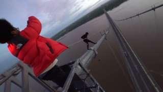 Urban explorers climbing the Humber Bridge