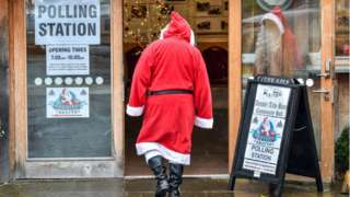 Santa goes to vote in Dunster Tithe Barn near Minehead, Somerset