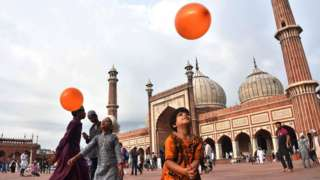 Indian children play with orange balloons