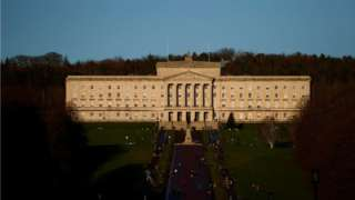 People walk through the grounds of the Stormont Parliament buildings in Belfast, Northern Ireland, on 30 December 2020.