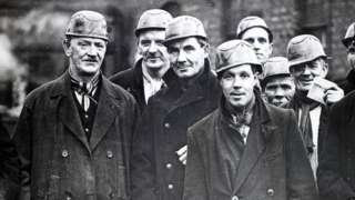 A group of miners at the West Cannock Colliery, Staffordshire, wearing helmets and carrying safety lamps, circa 1940.