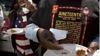 A man in a Juneteenth shirt holds a plate