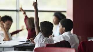 Raised hands in classroom