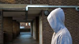 Man in grey hoodie in block of flats