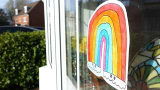 A picture of a rainbow is seen in a window