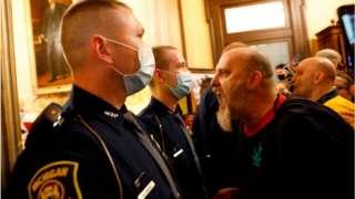A protester screams in a cops face