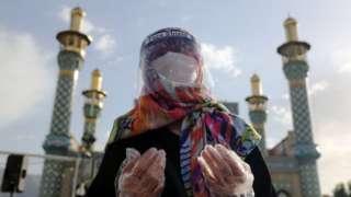 A worshipper in Tehran, Iran wears protective equipment