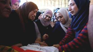 Relatives of Mohammed al-Alami mourn during his funeral near Hebron in the occupied West Bank (29 July 2021)