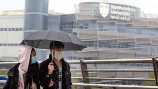 Two people wearing face masks walking together with a Northumbria University building seen in the background