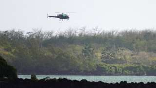 Search and rescue helicopter flies over the site of the collision off Mauritius on 31 August 2020