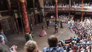 Audience members watch a production of A Midsummer Night's Dream at Shakespeare's Globe theatre