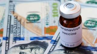 UKRAINE -2020/04/08: In this photo illustration a vial labelled Coronavirus vaccine seen displayed on one hundred US dollar banknotes.
