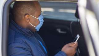 Man uses phone in taxi