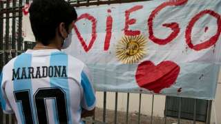 A fan wearing a Maradona Argentina shirt looks at a tribute in Buenos Aires