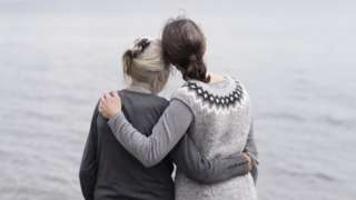 Older and younger woman embracing by the sea - posed by models